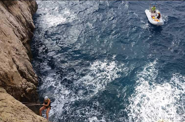 Una lancha sobre el mar y un escalador en la roca